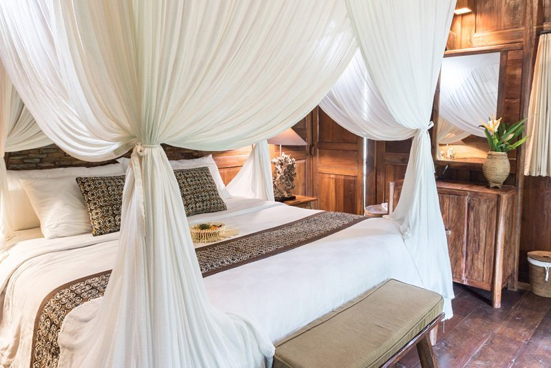 Bed with canopy in private villa in the accommodation Madani Antique Villas - Tegallalang, Bali