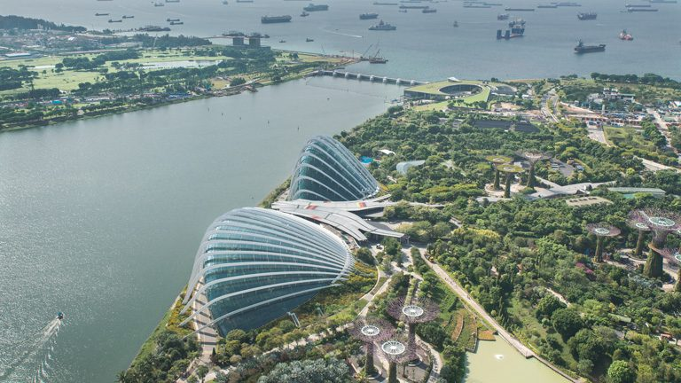 """Aerial view of the Gardens by the Bay from Sands SkyPark, with Marina Barrage  in the background"""