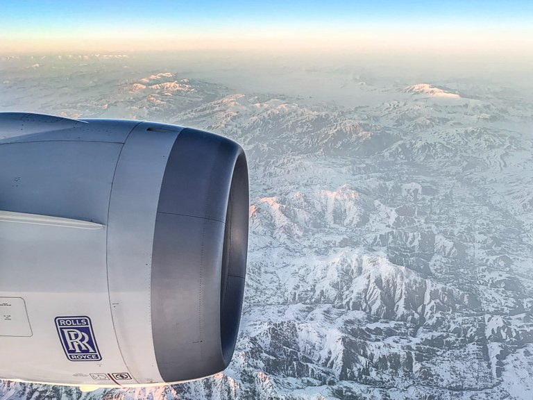 View from an airplane window with snowed mountains in Asia