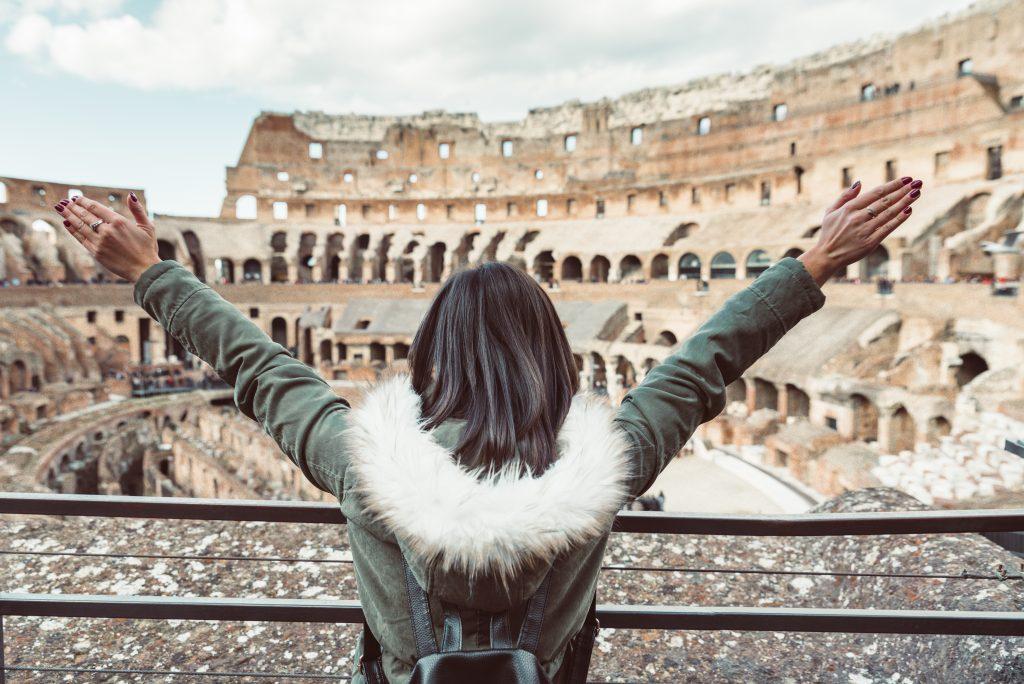 Mujer levantando los brazos en señal de alegría en el interior del Coliseo
