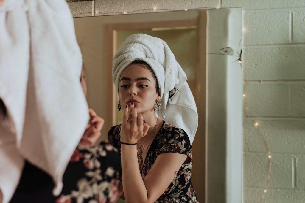 Mujer arreglándose en el espejo, nicho moda y belleza blog We Collect Postcards