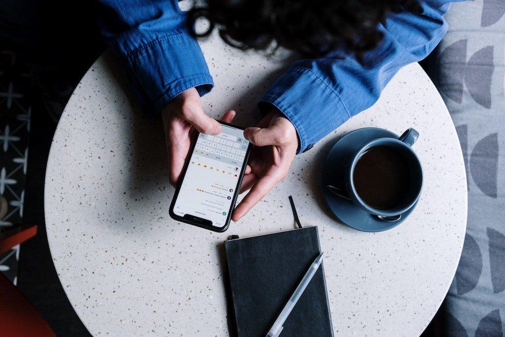 Hombre gestionando sus redes sociales en una cafetería