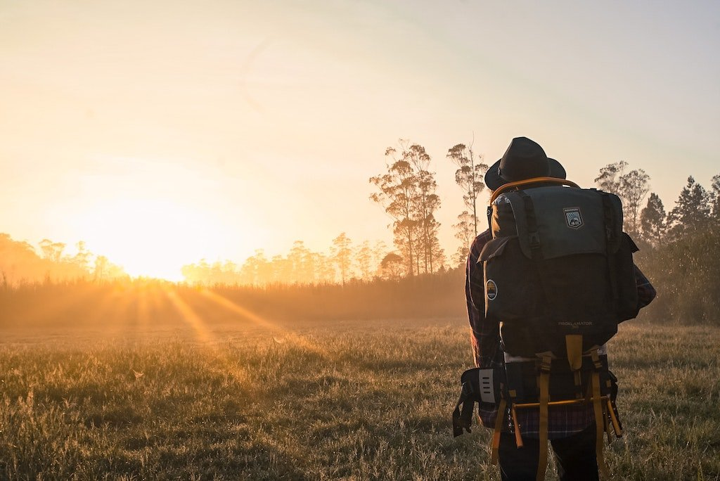 Hombre viajero con una mochila en la espalda viendo la puesta del sol, blog We Collect Postcards