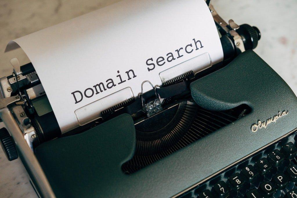 Máquina de escribir con un papel blanco con texto Domain Search