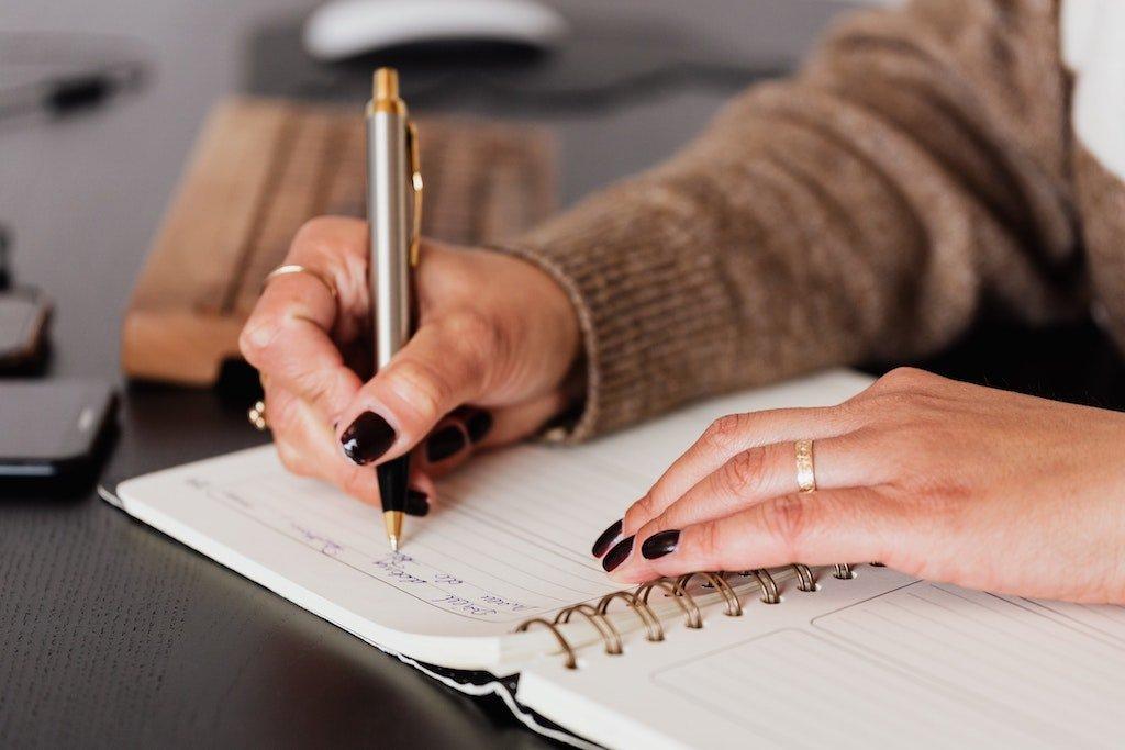 Manos de una mujer planificando sus tareas escribiendo en una libreta
