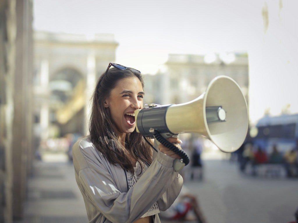 Mujer con un megáfono dirigiéndose sonriendo a su audiencia