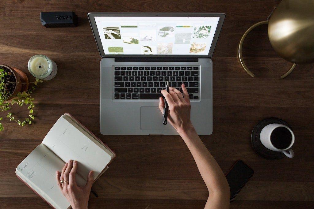 Manos de una mujer trabajando con su portátil y un cuaderno de notas para encontrar un nicho para su blog