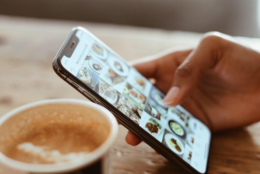 Imagen de una mano de mujer sujetando un smartphone y viendo las redes sociales, blog We Collect Postcards