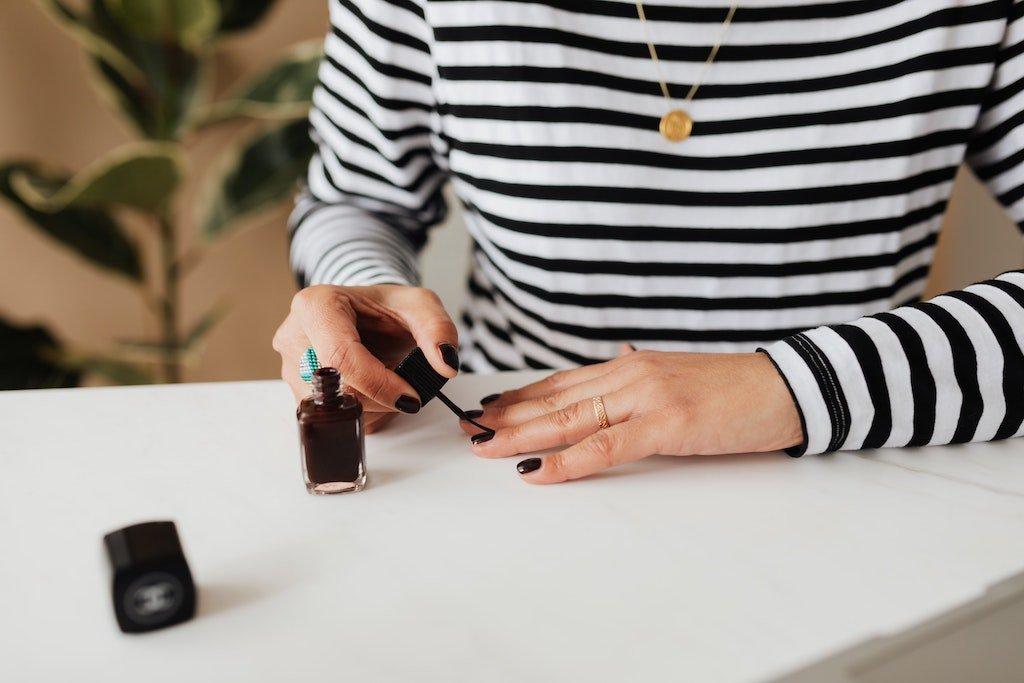 Mujer con una camiseta de rayas pintándose las uñas en casa
