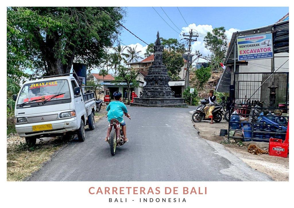 Postal con una imagen de un niño conduciendo una moto por las carreteras de Bali