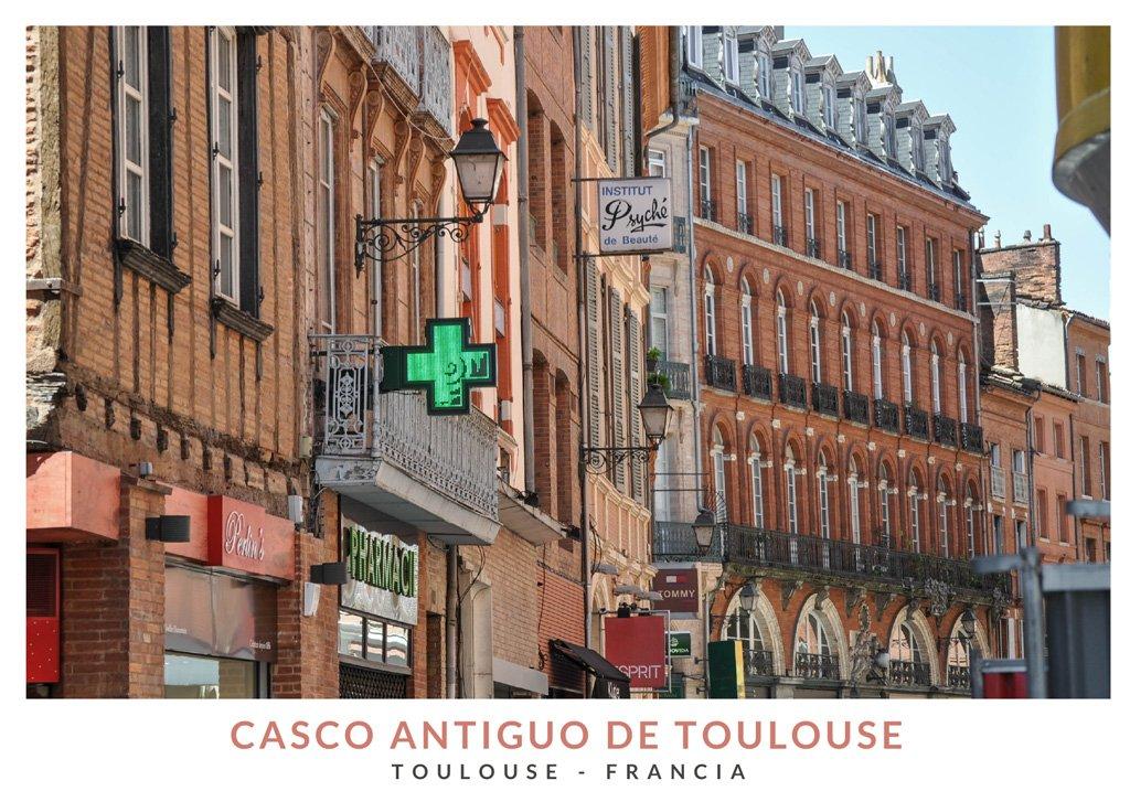 Calle con edificios en tonos rosa y naranja en el casco antiguo de Toulouse