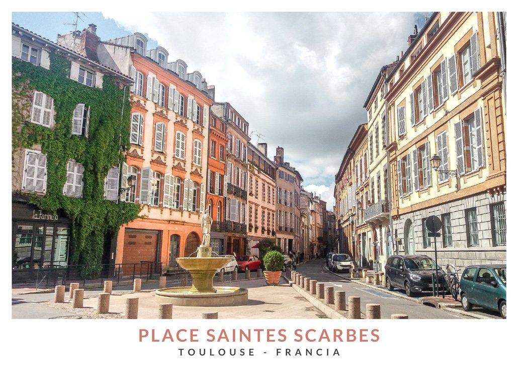 Plaza Saintes Scarbes de Toulouse con una fuente en medio y edificios de color rosa y naranja