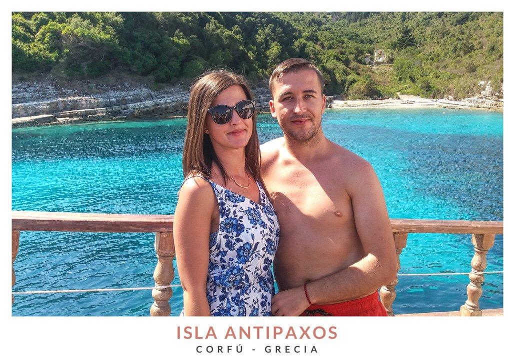 Pareja jóven en un barco con la Playa Voutoumi y aguas turquesas de fondo en Antipaxos, Grecia