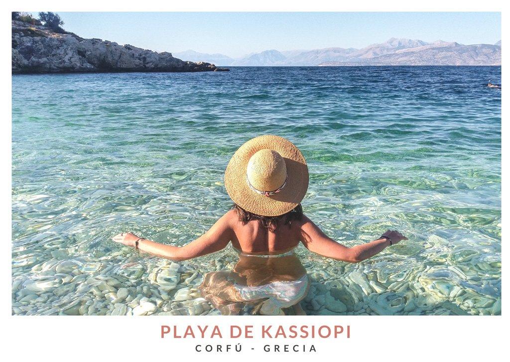 Mujer jóven con sombrero de espaldas en la playa de Kassiopi en Corfú, Grecia